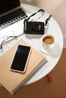 Bureau avec téléphone portable, tasse à café, ordinateur portable, appareil photo et lunettes