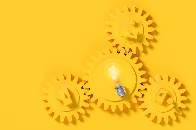 Bureau de travail et ampoule de couleur jaune sur l'engrenage avec espace de copie pour votre texte.