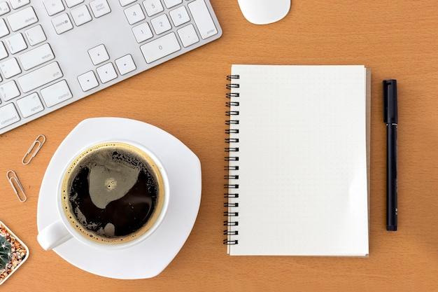 Bureau de travail avec clavier, bloc-notes, souris et café de tasse sur la table en bois. à la lumière