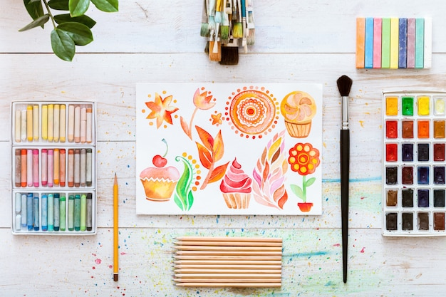 Bureau de travail créatif avec des pinceaux sur fond de bois blanc, mise à plat