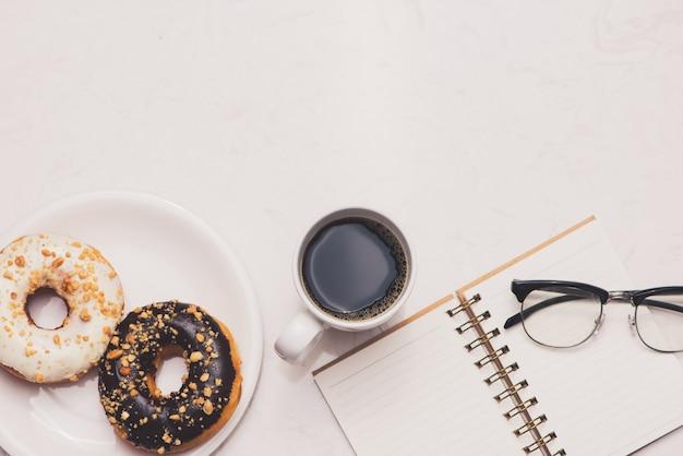 Bureau de travail avec dessert et café. beignets de gâteau avec une tasse d'espresso sur une table en marbre.