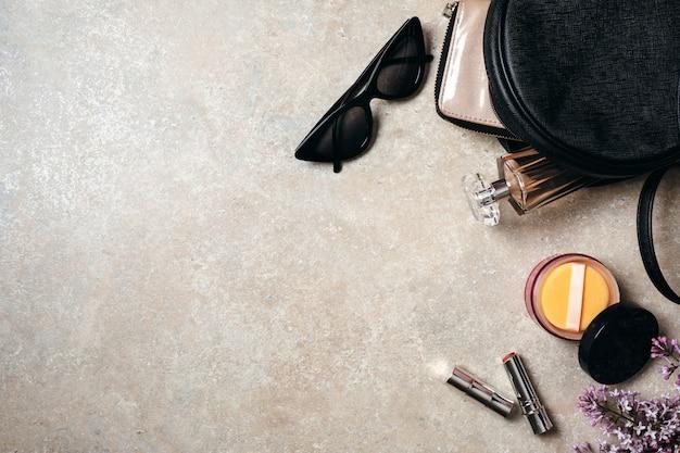 Bureau de travail à la maison minimaliste moderne avec des lunettes de soleil, un sac en cuir, un portefeuille, une femme cosmétique, des fleurs de printemps lilas sur fond de pierre en béton.