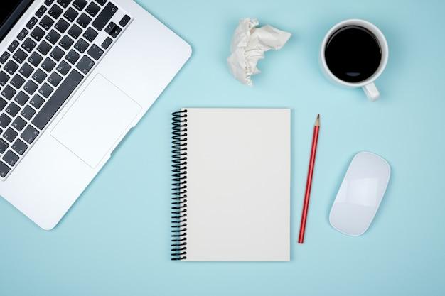 Bureau de travail minimal avec ordinateur portable et page de bloc-notes vierge