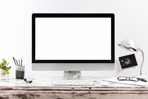 Bureau de travail minimaliste avec écran blanc