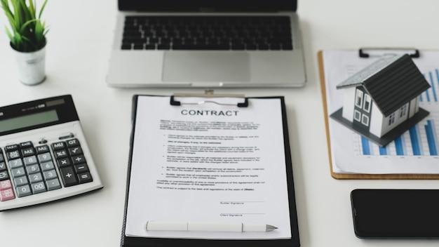 Bureau de travail pour la signature de documents de contrat de construction de maison avec maison modèle sur graphique et ordinateur portable, calculatrice, smartphone sur table, concept de signature immobilière, vue de dessus.