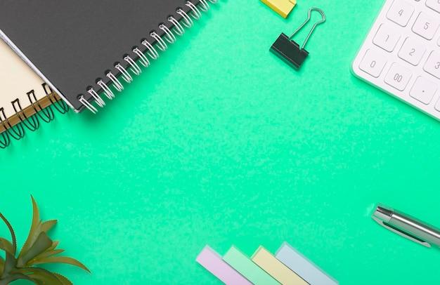 Bureau vert ou fond de table. toile de fond avec plante, calculatrice, stylo et cahier à spirale.