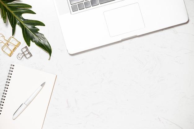 Bureau vue de dessus avec clavier, cahiers et tasse à café sur fond de marbre.