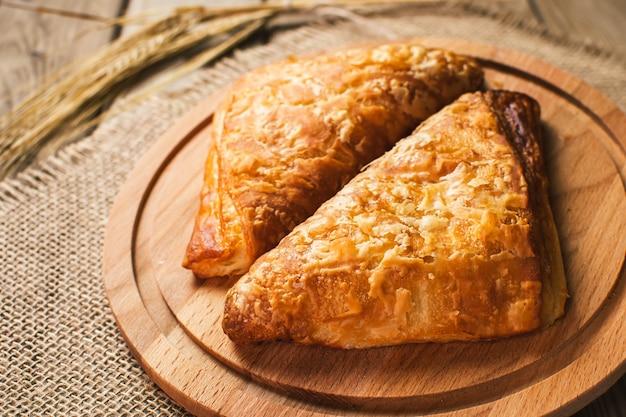 Burekas remplis de fromage sur une table en bois et une planche à découper. fraîchement cuit.