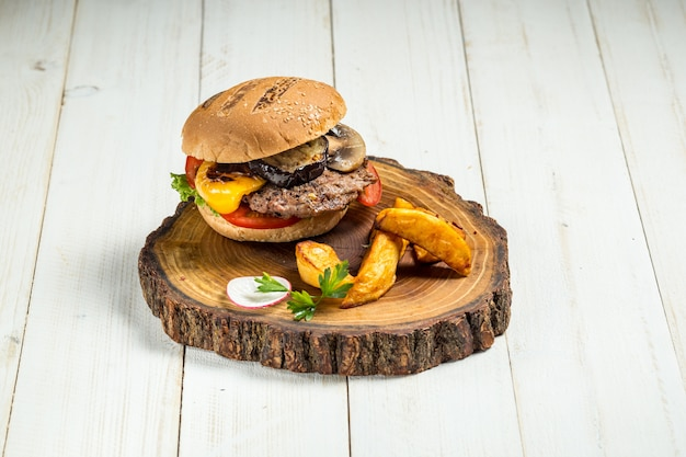 Burger américain aux aubergines et quartiers de pommes de terre sur fond de bois blanc