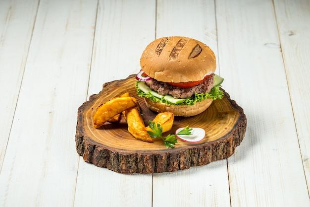 Burger américain aux aubergines et quartiers de pommes de terre sur planche de bois