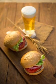 Burger au fromage avec viande grillée, fromage, tomate, sur papier craft sur la surface en bois.