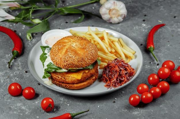 Burger au poulet avec frites et salade sur une vieille table en béton