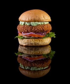 Burger au poulet avec laitue, tomate, oignon violette et mayo à la main sur backgorund noir. délicieux.