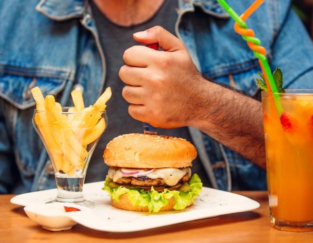 Burger au poulet avec oignons rouges, fromage fondu, concombre mariné, laitue, tomate