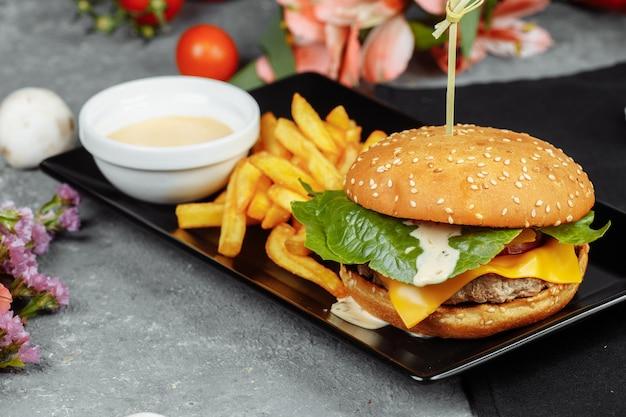 Burger aux escalopes et tomates avec frites et sauce burger