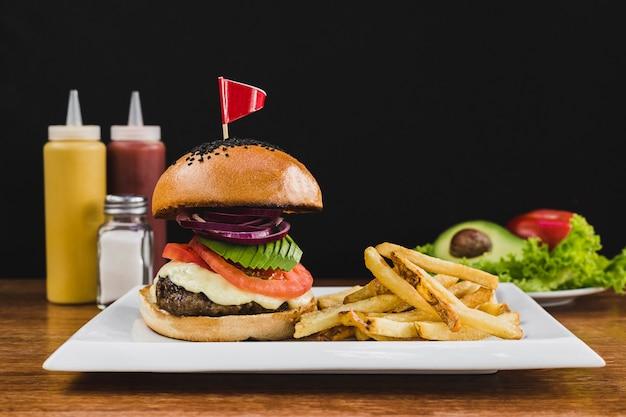 Burger à l'avocat, tomate, oignon, fromage et frites
