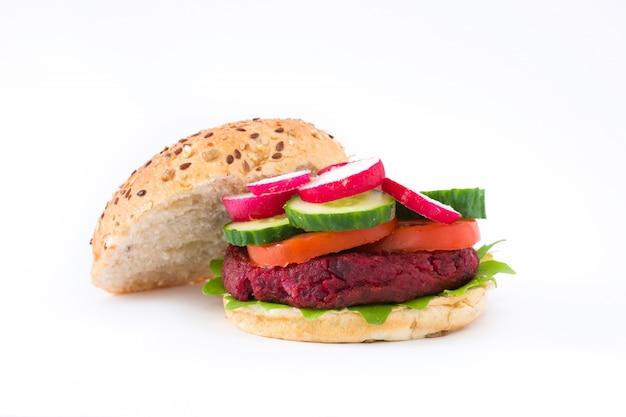 Burger de betteraves végétaliennes avec laitue d'agneau, tomate, concombre et radis isolé sur surface blanche