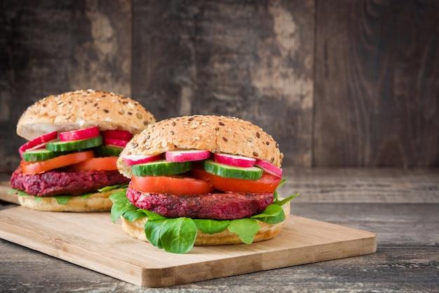 Burger de betteraves végétariennes avec laitue d'agneau, tomate, radis et concombre sur l'espace de copie de table en bois rustique