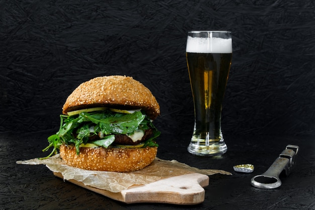 Burger et bière dans un verre sur fond sombre. hamburger