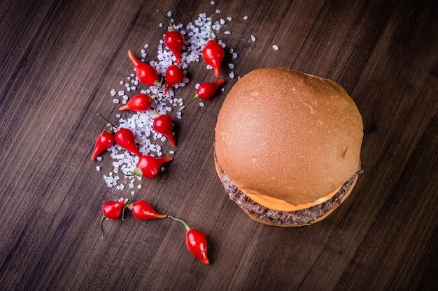 Burger de bœuf double-artisanal avec fromage cheddar, oignon caramélisé et louche de poivre sur table en bois