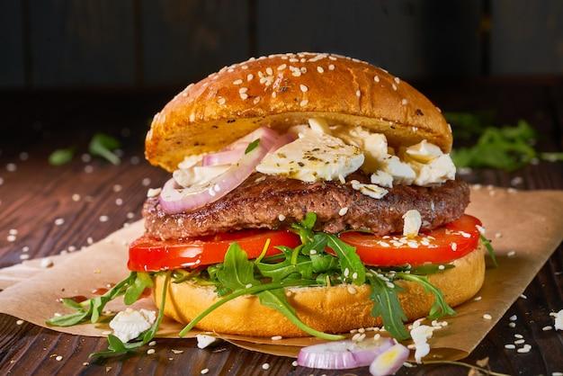 Burger de boeuf fait maison avec roquette et tomates servi sur table en bois