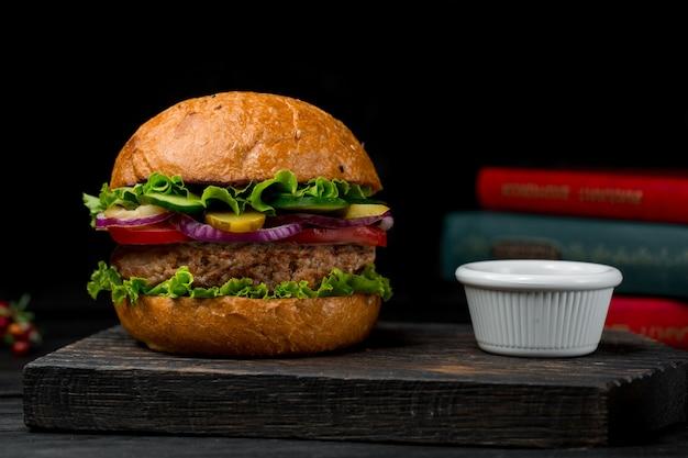 Burger de boeuf farci avec des ingrédients mélangés sur un tableau noir