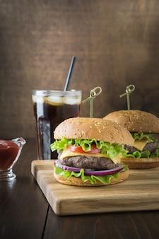 Burger de boeuf frais avec boisson sur planche de bois. orientation horizontale. espace pour le texte.