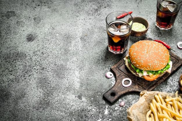 Burger de boeuf frais avec cola et frites. sur un fond rustique.