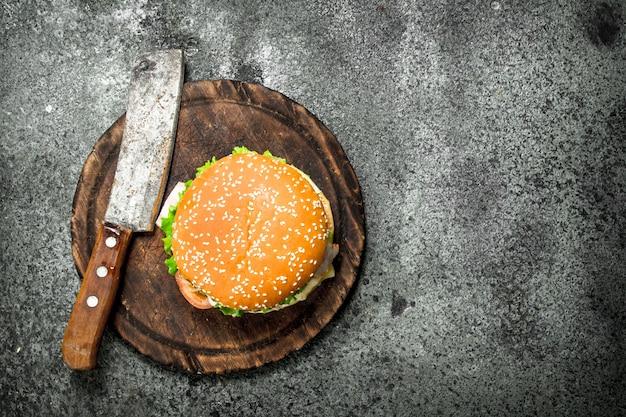 Burger de boeuf frais avec un couteau sur la planche. sur une table rustique.