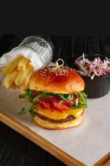 Burger de bœuf juteux à la sauce de airelles, fromage fondu, roquette, pommes de terre frites et chou rouge