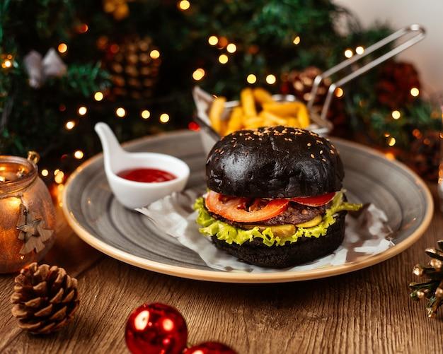 Burger de boeuf noir servi avec du ketchup de frites et de la mayonnaise