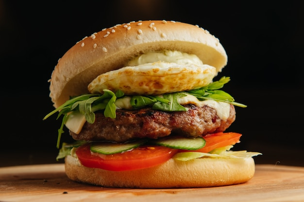 Burger de boeuf avec oeuf poché. hamburger - pain, hamburger à la viande grillée, salade de roquette, tomate et œuf au plat.