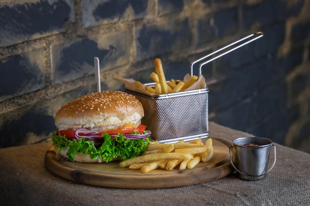 Burger de boeuf savoureux avec des frites sur la plaque de bois avec souce. fond de mur sombre et brique