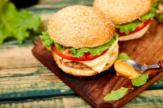 Burger de boeuf sur une table en bois isolée sur fond noir.