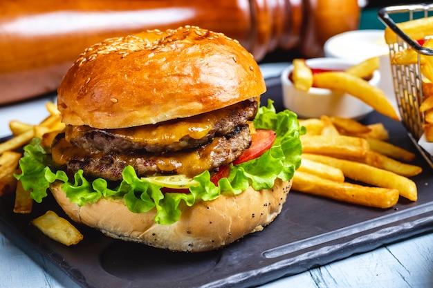 Burger de boeuf viande laitue fromage tomate frites vue latérale