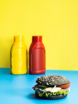 Burger avec des bouteilles de ketchup et de moutarde