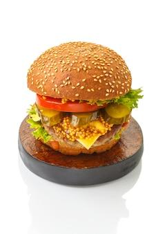Burger classique au boeuf, fromage légumes en sauce sur un petit pain aux graines de sésame sur un support rond brun sur une plaque de bois