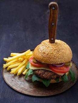 Burger avec côtelette, tomate, fromage et frites