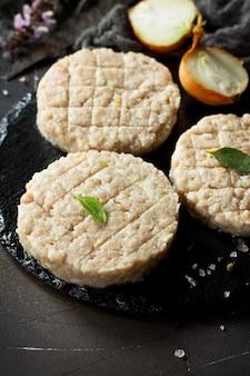 Burger de côtelettes fraîches crues de boeuf pour des hamburgers faits maison cuisinant avec des épices sur tableau noir