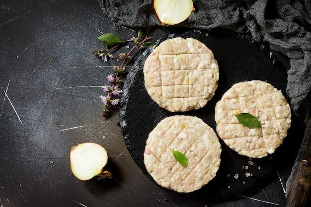 Burger de côtelettes fraîches crues de boeuf pour des hamburgers faits maison cuisinant avec des épices