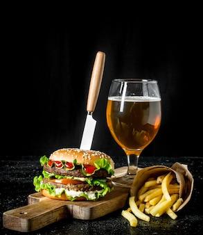 Burger avec un couteau, frites, bière dans un verre. sur fond rustique noir