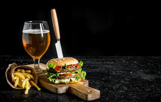 Burger avec un couteau, frites, bière dans un verre sur table en bois noir