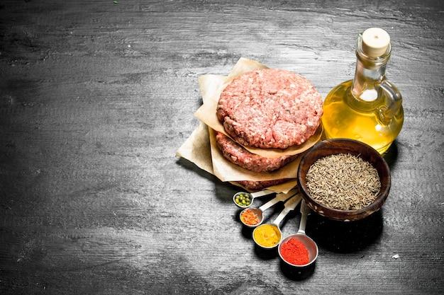 Burger cru aux épices et herbes. sur le tableau noir.