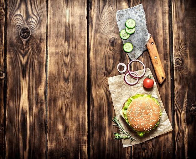 Burger cuit avec des légumes, du fromage et de la viande. sur fond de bois. vue de dessus.