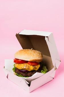 Burger dans une boîte blanche sur fond rose