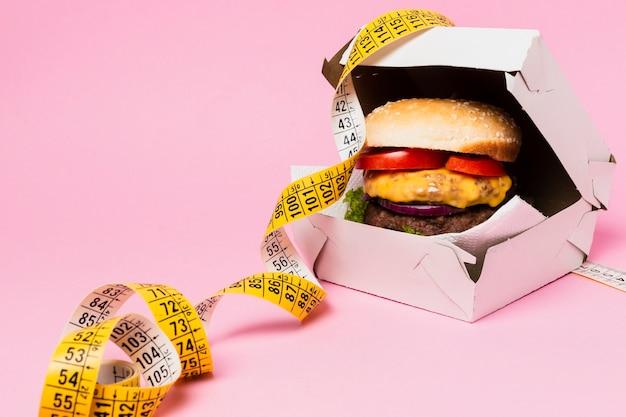 Burger dans une boîte blanche avec un ruban à mesurer