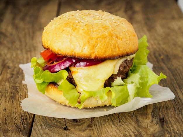 Burger délicieux avec côtelette de boeuf, fromage, oignon, tomate et laitue sur petits pains grillés.