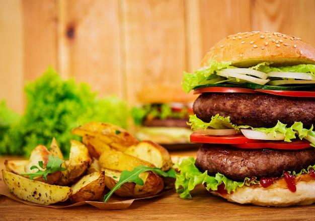 Burger délicieux à la main sur bois. vue rapprochée