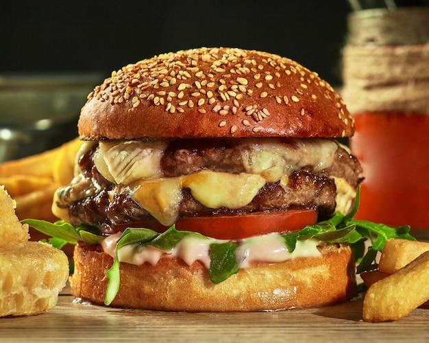 Burger avec deux galettes de tomates au fromage et légumes verts dans un petit pain au sésame