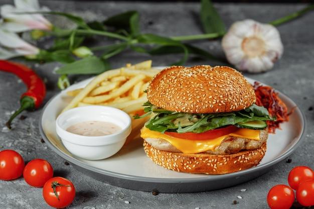 Burger de dinde sur un petit pain avec du fromage, de la laitue, des tomates et du concombre frais. burger avec escalope de viande de dinde sur fond gris avec des frites